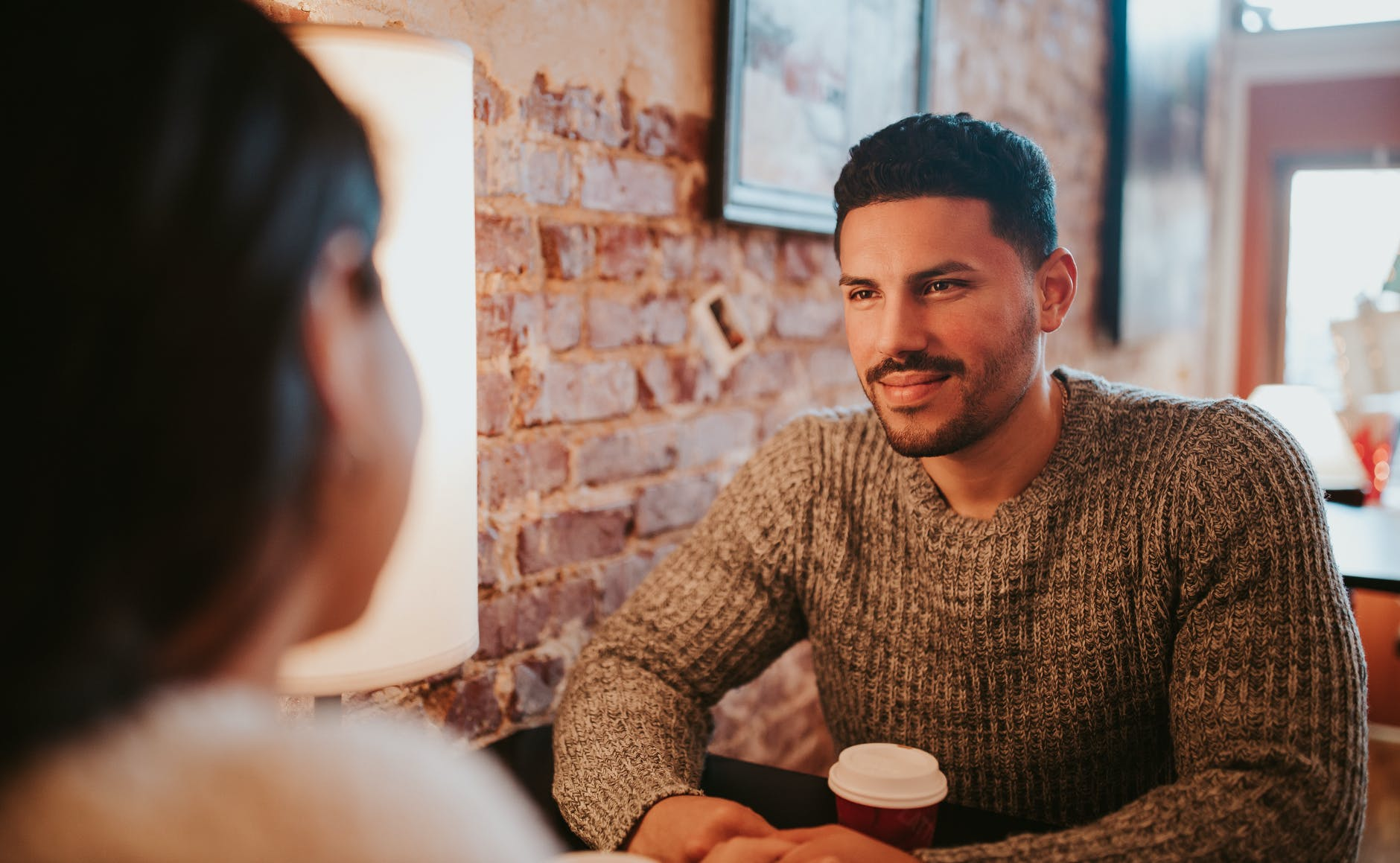 couple sitting at cafe together with coffee cup